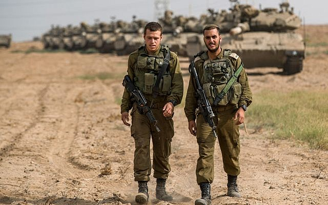 Israeli soldiers seen walking next to Merkava tanks that are stationed in an open area near Israel's border with the Gaza Strip on October 19, 2018  Photo by: JINIPIX