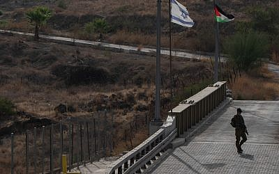 A Picture taken from the Israeli side of the border fence in Naharayim also known by Jordanians as Baqura on October 22, 2018, shows Israeli soldier standing on the wat to the Jordanian army outpost as well as Israeli (R) and Jordanian flags, in the Jordan valley in Northern Israel. - Jordan's King Abdullah II announced on October 21, 2018 that Jordan has notified Israel it wants to reclaim two small plots of territory leased under their 1994 peace deal, but Israel's Prime Minister Benjamin Netanyahu said he wanted to open negotiations to keep the current arrangement in place. Photo by: Ayal Margolin-JINIPIX