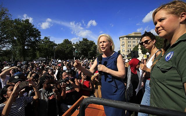 Sen. Kirsten Gillibrand, with actress and comedian Amy Schumer, right, and actress model Emily Ratajkowski, centre, speaks at a rally against Supreme Court nominee Brett Kavanaugh at the Supreme Court in Washington (AP Photo/Manuel Balce Ceneta)