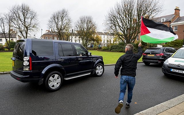 A protester waving the Palestinian flag runs alongside the vehicle of the Israeli ambassador to the United Kingdom Mark Regev as he departs after visiting Queen's University, Belfast. Photo credit: Liam McBurney/PA Wire