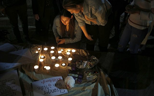 People light candles  in Tel Aviv, Israel, in a commemoration of the victims of a deadly shooting at a Pittsburgh synagogue, Sunday, Oct. 28, 2018. (AP Photo/Ariel Schalit)
