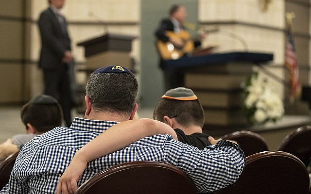 People gather at the B'nai Aviv Synagogue in Weston, Fla., Sunday, Oct. 28, 2018, after Saturday's shooting that took place during worship services inside Tree of Life Synagogue in Pennsylvania. (Jennifer Lett/South Florida Sun-Sentinel via AP)