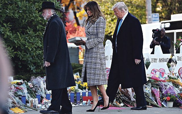 President Donald Trump, right, First Lady Melania Trump place stones and flowers on a memorial at the Tree of Life Synagogue in Pittsburgh, Pa, Oct. 30, 2018. Rabbi Jeffrey Myers joins them.   Credit: Mykal McEldowney/Indianapolis Star via USA TODAY NETWORK/Sipa USA