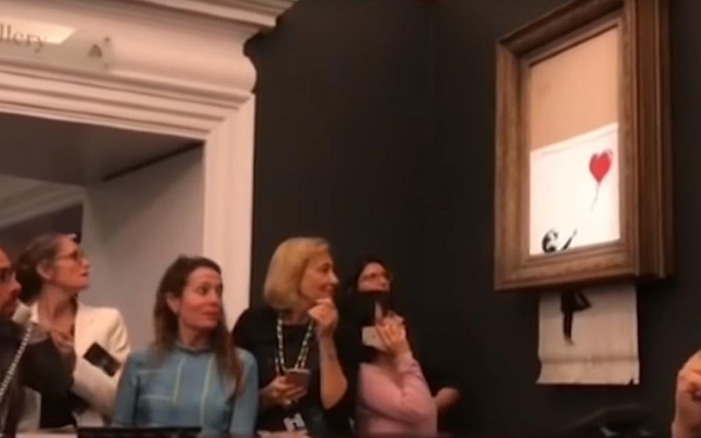 Screenshot from YouTube video showing Bansky shredding his own artwork