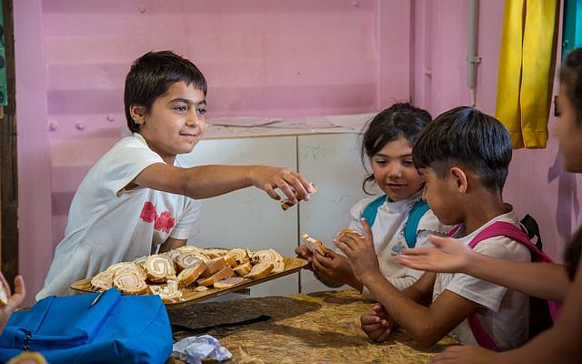 Children share treats in the School of Peace, Lesbos. Photo Credit - Lisa Kristine