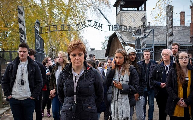 Nicola Sturgeon at Auschwitz, in front of the gate reading 'Work sets you free - Arbeit macht frei' (Credit: Holocaust Educational Trust)