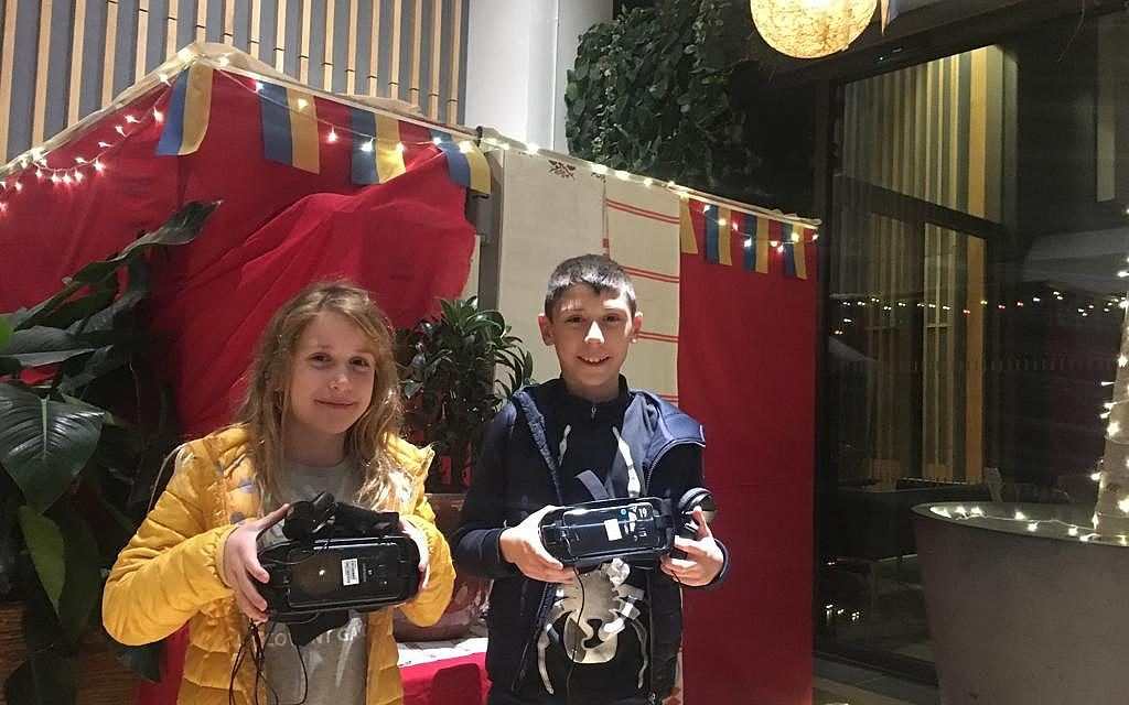 Two young attendees of the World Jewish Relief event at JW3, experience Ukrainian food through special 4D 'virtual reality'