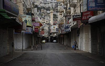 A Palestinian man walks in front of closed shops during a general strike in protest of the recently passed Jewish nation state law in Israel. in the old city of Nablus in the West Bank. (AP Photo/Majdi Mohammed)