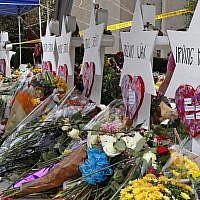 Flowers surround Stars of David as part of a makeshift memorial outside the Tree of Life Synagogue to the 11 people killed during worship services Saturday Oct. 27, 2018 in Pittsburgh. (AP Photo/Gene J. Puskar)