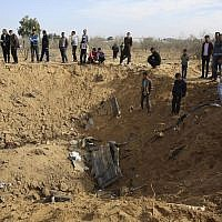 """Palestinians inspect a crater and the wreckage of vehicles destroyed by an Israeli raid that killed seven Hamas Palestinian militants late Sunday, east of Khan Younis, southern Gaza Strip, Monday, Nov. 12, 2018. Chanting """"revenge"""" and flanked by masked gunmen in camouflage, thousands of mourners in the Gaza Strip on Monday buried the seven who were killed in the Israeli incursion as the ruling Hamas group launched a feverish security sweep across the territory. (AP Photo/Adel Hana)"""