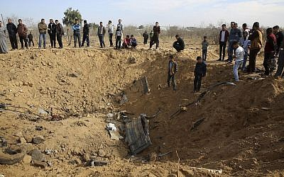 "Palestinians inspect a crater and the wreckage of vehicles destroyed by an Israeli raid that killed seven Hamas Palestinian militants late Sunday, east of Khan Younis, southern Gaza Strip, Monday, Nov. 12, 2018. Chanting ""revenge"" and flanked by masked gunmen in camouflage, thousands of mourners in the Gaza Strip on Monday buried the seven who were killed in the Israeli incursion as the ruling Hamas group launched a feverish security sweep across the territory. (AP Photo/Adel Hana)"