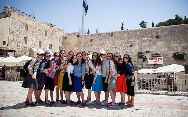 Teenage girls on tour in Israel posing in front of the Western Wall