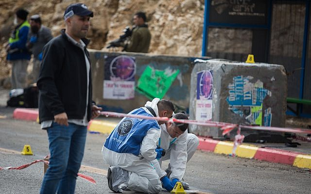 """Israeli forces and forensics inspect the site of a Palestinian drive-by shooting attack outside the West Bank settlement of Givat Asaf, northeast of Ramallah, on December 13, 2018. - Two Israelis were killed and at least two others were wounded at the bus stop in the occupied West Bank, the army said. """"A Palestinian opened fire at a bus stop killing 2 Israelis, severely injuring 1 & injuring others at Asaf Junction, north of Jerusalem,"""" the Israeli military said on its Twitter account. Photo by: JINIPIX"""