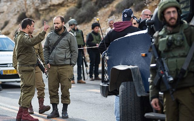 Israeli forces  inspect the site of a Palestinian drive-by shooting attack outside the West Bank settlement of Givat Asaf, northeast of Ramallah, on December 13, 2018. - Two Israelis were killed and at least two others were wounded at the bus stop in the West Bank Photo by: JINIPIX