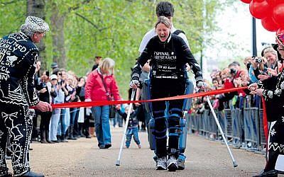Claire crossing the finish line in London in her ReWalk suit.