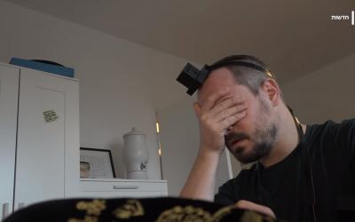 Yonatan Langer does tefillin (Screenshot from Kan News' video)