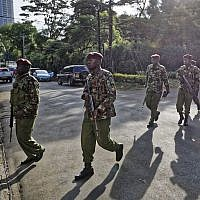 Security forces walk to the scene as continued blasts and gunfire could be heard early Wednesday, Jan. 16, 2019 in Nairobi, Kenya.  (AP Photo/Ben Curtis)