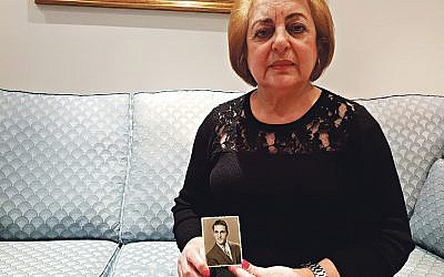Faiza Saigh holding a photo of her brother, Daoud Ghali Yadgar