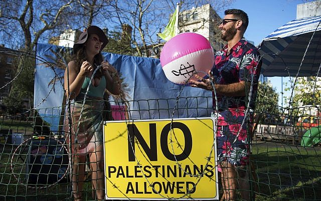 """Two models stand on a """"barbed-wire beach"""" outside the offices of TripAdvisor in Soho Square, as part of an Amnesty International campaign calling on the firm and other travel companies to stop listing rooms and activities in Israeli settlements in the Palestinian Territories.  Photo credit: Kirsty O'Connor/PA Wire"""