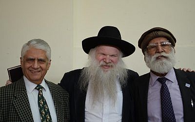 Rabbi Herschel Gluck with two guests at the exhibition