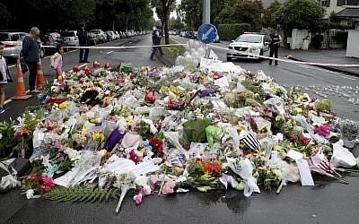 Mourners place flowers as they pay their respects at a makeshift memorial near the Masjid Al Noor mosque in Christchurch, New Zealand (AP Photo/Mark Baker)