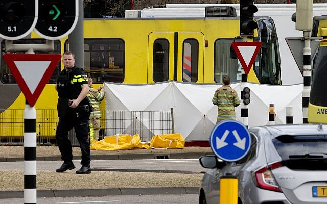 Rescue workers install a screen on the spot where a body was covered with a white blanket following a shooting in Utrecht (AP Photo/Peter Dejong)