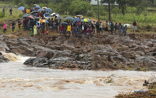 Schoolchildren are stranded across a collapsed bridge in Chimanimani, southeast of Harare, Zimbabwe, Monday, March 18, 2019. (AP Photo/Tsvangirayi Mukwazhi)