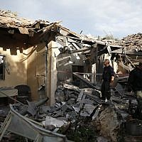 Police officers inspect the damage to a house hit by a rocket in Mishmeret, central Israel, Monday, March 25, 2019. (AP Photo/Ariel Schalit)