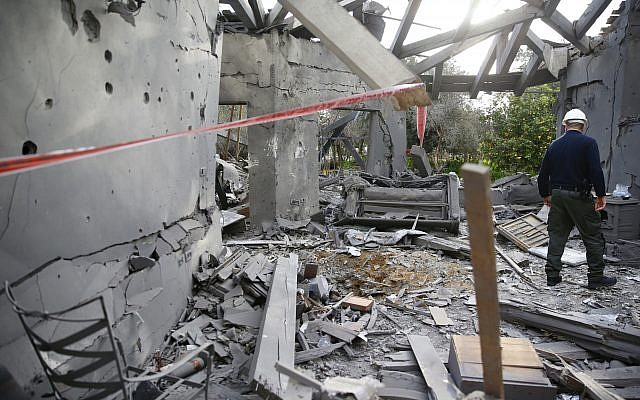 A police officer inspects the damage to a house hit by a rocket in Mishmeret, central Israel. (AP Photo/Ariel Schalit)
