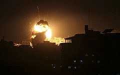 An explosion caused by Israeli airstrikes is seen from the offices of Hamas leader Ismail Haniyeh, in Gaza City, Monday, March 25, 2019. (AP Photo/Adel Hana)