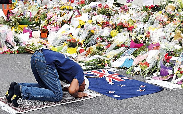 A Muslim worshipper prays at a makeshift memorial at the Al Noor Mosque on Deans Rd in Christchurch, New Zealand. (AAP Image/Mick Tsikas)