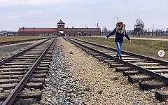 Picture posted by the Auschwitz Museum showing a visitor balancing on the tracks