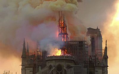 Flames and smoke rise as the spire of Notre Dame cathedral is on fire in Paris, Monday, April 15, 2019. (AP Photo/Dominique Bichon)