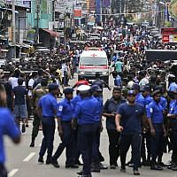 Sri Lankan police officers clear the road as an ambulance drives through carrying injured of Church blasts in Colombo, Sri Lanka, Sunday, April 21, 2019. A Sri Lanka hospital spokesman says several blasts on Easter Sunday have killed dozens of people. (AP Photo/Eranga Jayawardena)