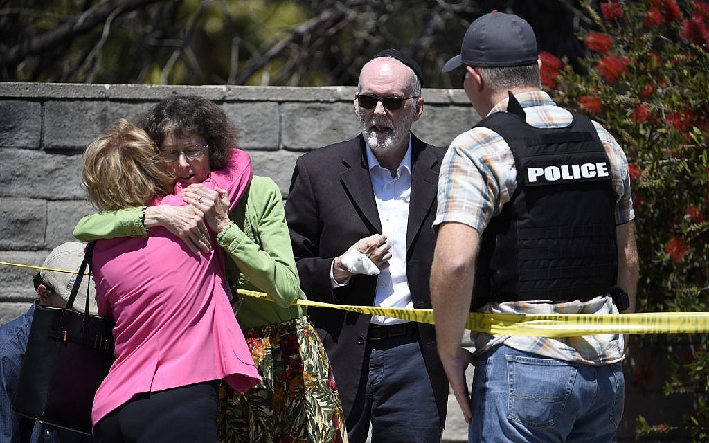 Two people hug as another talks to a San Diego County Sheriff's deputy outside of the Chabad of Poway Synagogue Saturday, April 27, 2019, in Poway, Calif. (AP Photo/Denis Poroy)