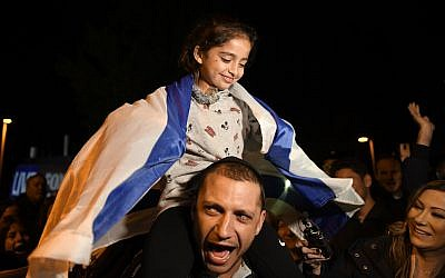 Noya Dahan, 8, rides on the shoulders of her father, Israel Dahan, at a candlelight vigil held for victims of the Chabad of Poway synagogue shooting, Sunday, April 28, 2019, in Poway, Calif. . (AP Photo/Denis Poroy)