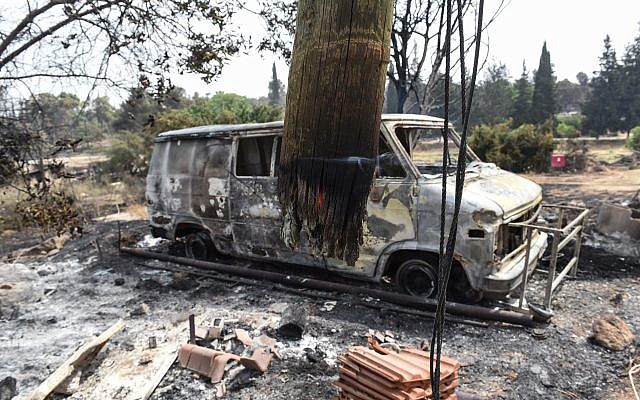 Charred SUV car and a damaged building are pictured in the village of Mevo Modi'im, in central Israel on May 24, 2019 following a fire amidst extreme heat wave. Photo by: JINIPIX