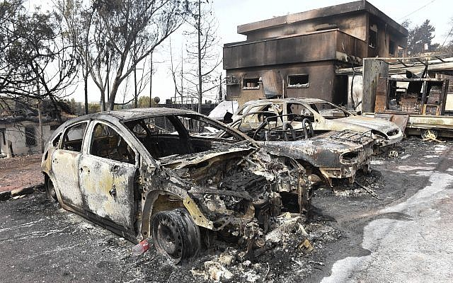 Charred cars and a damaged building are pictured in the village of Mevo Modi'im, in central Israel on May 24, 2019 following a fire amidst extreme heat wave. Photo by: JINIPIX