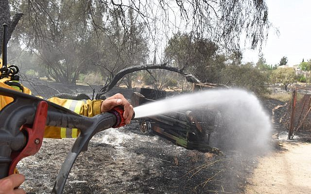 An Israeli firefighter sprays water on an agricultural machinery destroyed following a fire amidst extreme heat wave in the village of Mevo Modi'im, in central Israel on May 24, 2019. Photo by: JINIPIX