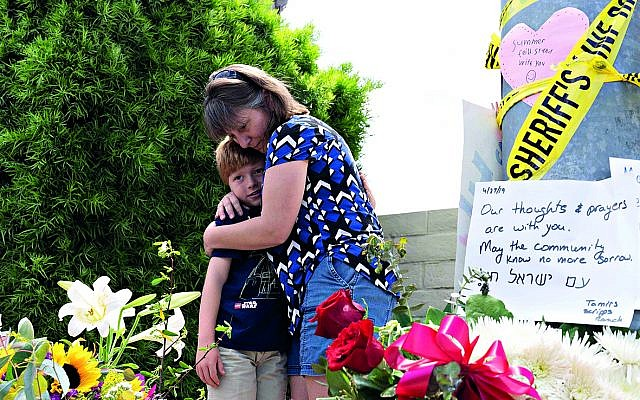 Heather Fay with her son Marshall came with flowers and notes at the memorial site across Chabad of Poway synagogue, while some of the eyewitnesses from the horrific incident gave a brief to media.   Credit: Nick Oza/The Arizona Republic via USA TODAY NETWORK/Sipa USA