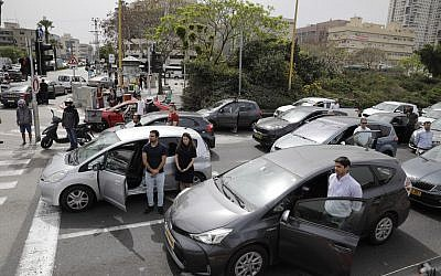 Israelis stand next to their cars as sirens mark a nationwide moment of silence in remembrance of the 6 million Jewish victims of the Holocaust, in Tel Aviv, Thursday, May 2, 2019. (AP Photo/Sebastian Scheiner)