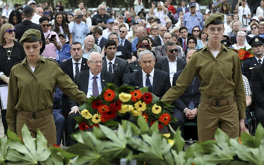 Israeli soldiers hold a wreath as Israeli Prime Minister Benjamin Netanyahu, center, Israeli President Reuven Rivlin, center left, and other guests attend the opening ceremony of Israel's annual Holocaust Remembrance Day, at Yad Vashem, the Holocaust Memorial, in Jerusalem, Thursday, May 2, 2019. The somber day is also marked by ceremonies and memorials at schools and community centers. Restaurants and cafes close, and TV and radio stations play quiet music and Holocaust-themed programs. (Abir Sultan/Pool Photo via AP)