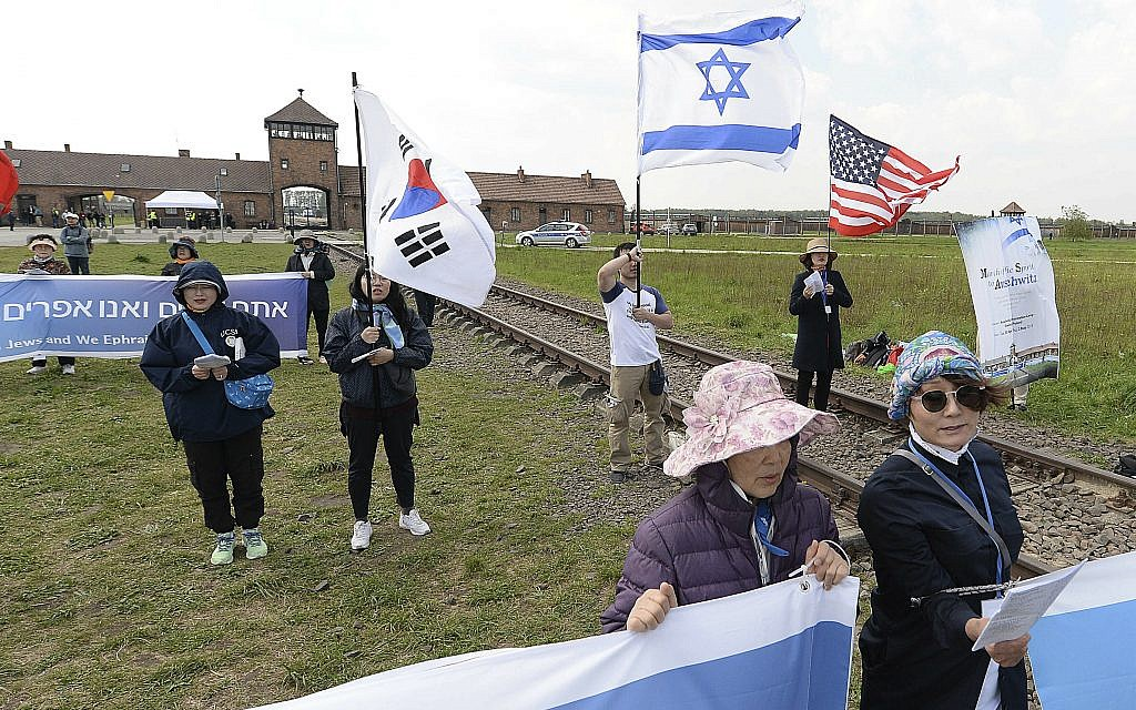 """People from South Korea around the world walk with Israeli flags through the former Nazi German death camp of Auschwitz-Birkenau during the annual Holocaust remembrance event, the """"March of the Living"""" in memory of the six million Holocaust victims in Oswiecim, Poland, Thursday, May 2, 2019. (AP Photo/Czarek Sokolowski)"""