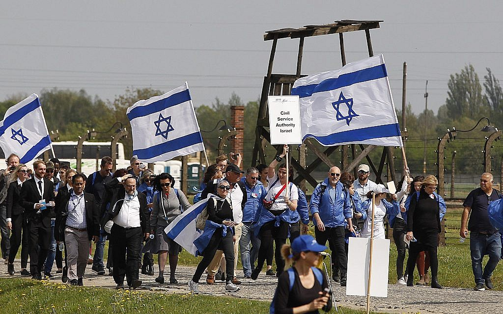 """Young Jews from around the world walk with Israeli flags through the former Nazi German death camp of Auschwitz-Birkenau during the annual Holocaust remembrance event, the """"March of the Living"""" in memory of the six million Holocaust victims in Oswiecim, Poland, Thursday, May 2, 2019.(AP Photo/Czarek Sokolowski)"""