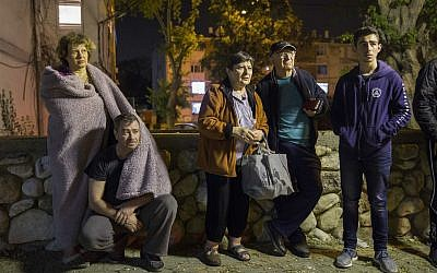 Israelis stand outside their building after it was hit by a rocket fired from Gaza in the costal city of Ashkelon, Israel, Sunday, May 5, 2019. Palestinian terrorists fired over 600 rockets into Israel, drawing dozens of retaliatory airstrikes on targets across the Gaza Strip in a round of intense fighting that broke a month-long lull between the bitter enemies (AP Photo/Tsafrir Abayov)