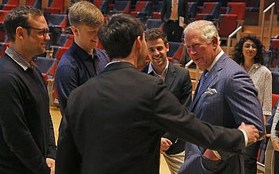 """David Strongin (centre) put his hand on the The Prince of Wales's shoulder before congratulating him on """"the English team's victory last night"""" during his visit to the Barenboim-Said Akademie, an academy located in Berlin, Germany, that offers bachelors degrees in music for talented young persons, most of them from the Middle East and North Africa. (Photo credit: Steve Parsons/PA Wire)"""