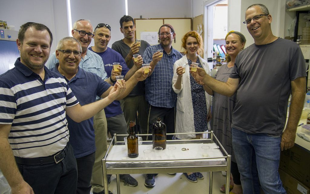 Team of researchers with new-old beer bottles produced in the labs. Photography: Yaniv Berman, courtesy of the Israel Antiquities Authority.