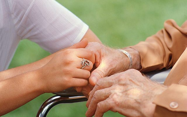 Nurse holding elderly person's hand