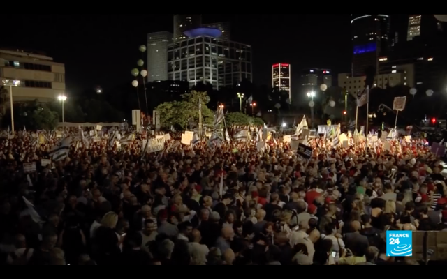 Screenshot from Youtube video from FRANCE 24 English of  thousands in Tel Aviv, protesting against Netanyahu.