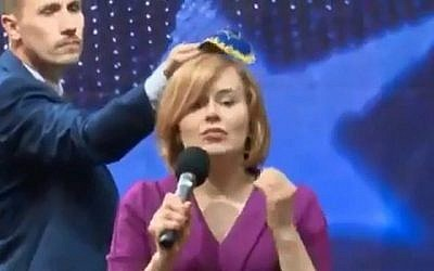 Polish politician Konrad Berkowicz puts a skullcap on the head of rival lawmaker Anna Krupka during a debate in Kielce on May 18, 2019. (screen capture: Twitter via Times of Israel)